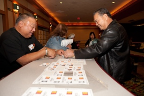 Dennis Kaneshiro picks up his badge from Bernie Imamura (husband of the late Susan Aoki)